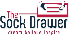 The Sock Drawer styled logo text shown with an illustration of a box with drawers. Dream, believe, inspire is written underneath the logo.